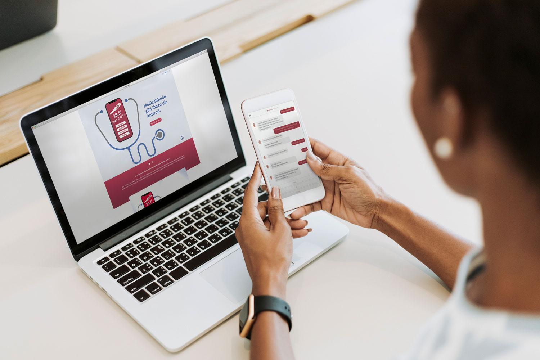 Frau mit geöffneter Medical-Guide-App auf dem Smartphone, im Hintergrund das MacBook mit der Landing Page des Medical Guides