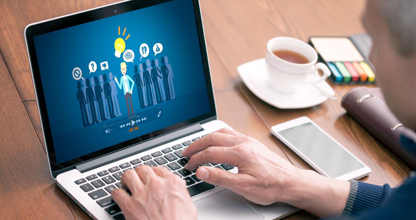 Mann, der sich am MacBook Pro das illustrierte Erklärvideo ansieht