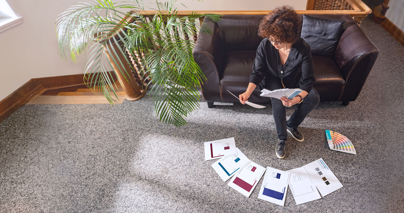 Marianne Kieser auf dem schwarzen Agentur-Sofa mit Pantonefächern und Proofs